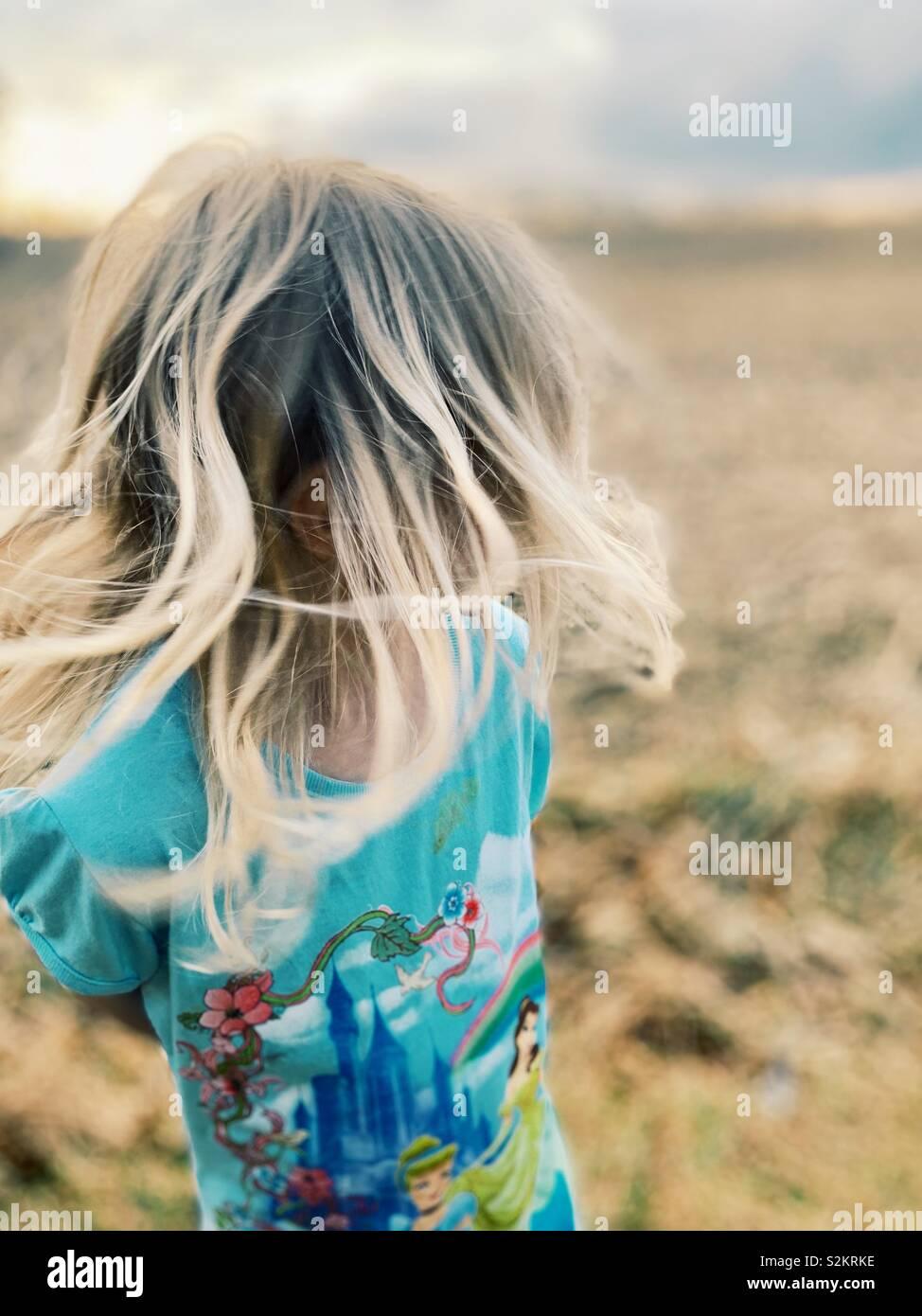 Chica con el pelo rubio en un campo. Foto de stock
