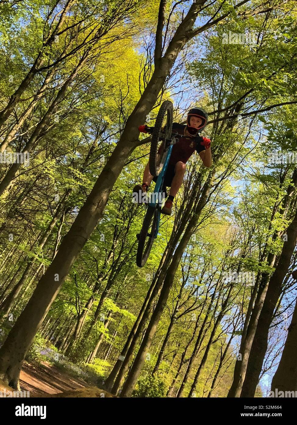 Ciclista de montaña obteniendo big air en un salto en el bosque Foto de stock