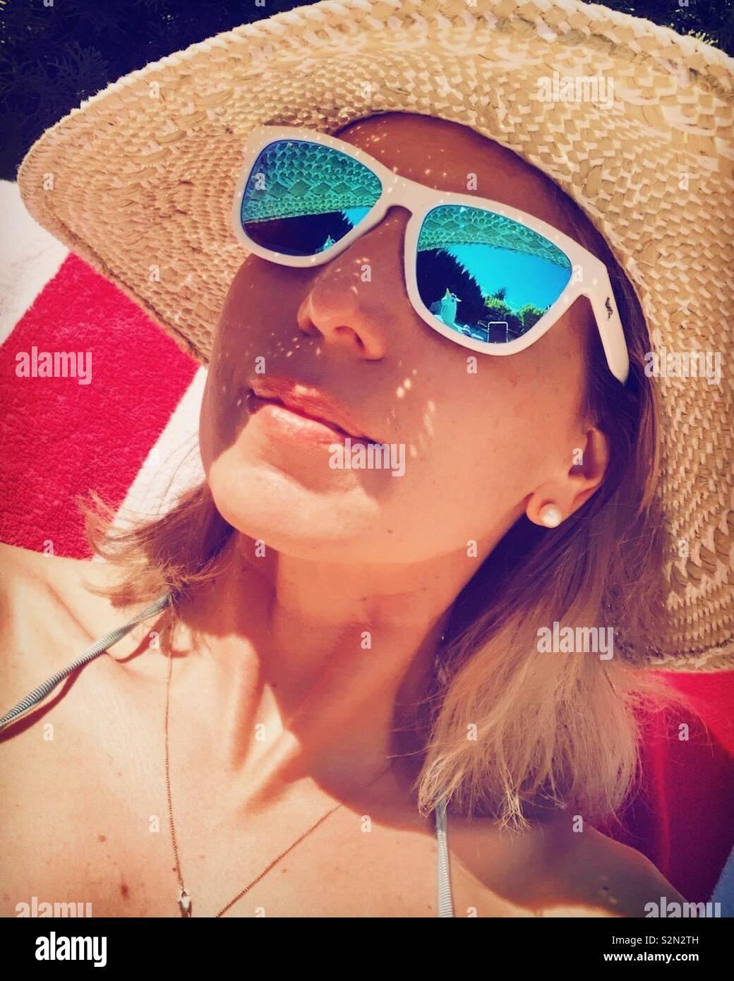 Mujer con gafas de sol y un sombrero de paja en un día soleado. Foto de stock