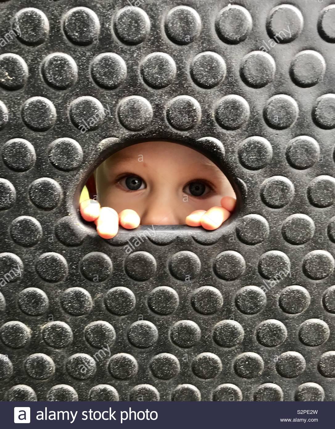 Un niño pares a través de un orificio de escalada en un gimnasio de la selva. Foto de stock