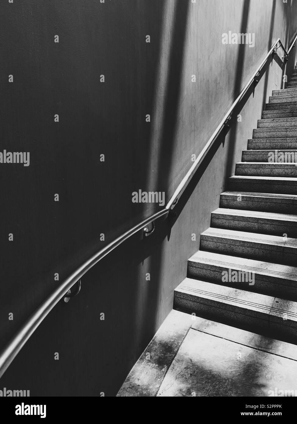 Escaleras arriba y sombras en blanco y negro Foto de stock