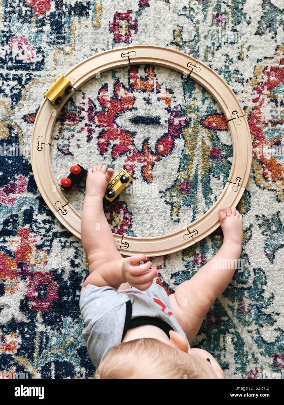 Vista aérea de un círculo pequeño tren de juguete vía y trenes en una colorida alfombra con las piernas de un bebé a través de la pista. Foto de stock