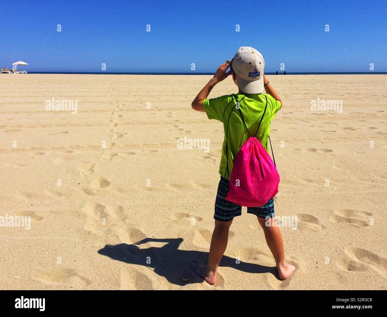 Vista trasera de un muchacho de pie en la playa Foto de stock