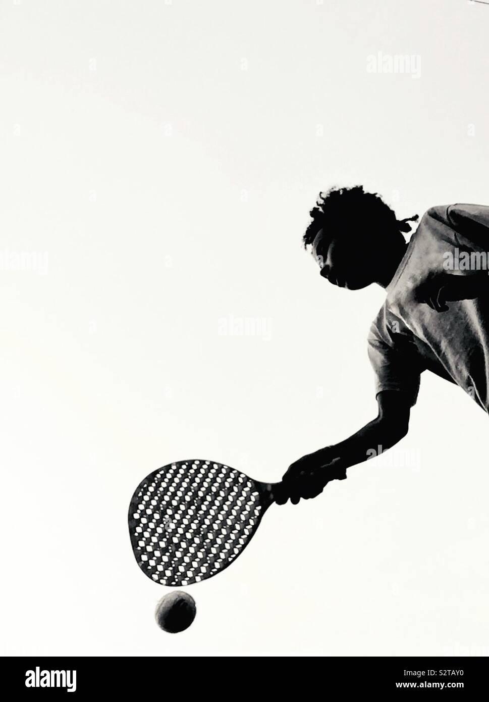 Un niño pagando con un bate y una pelota Foto de stock