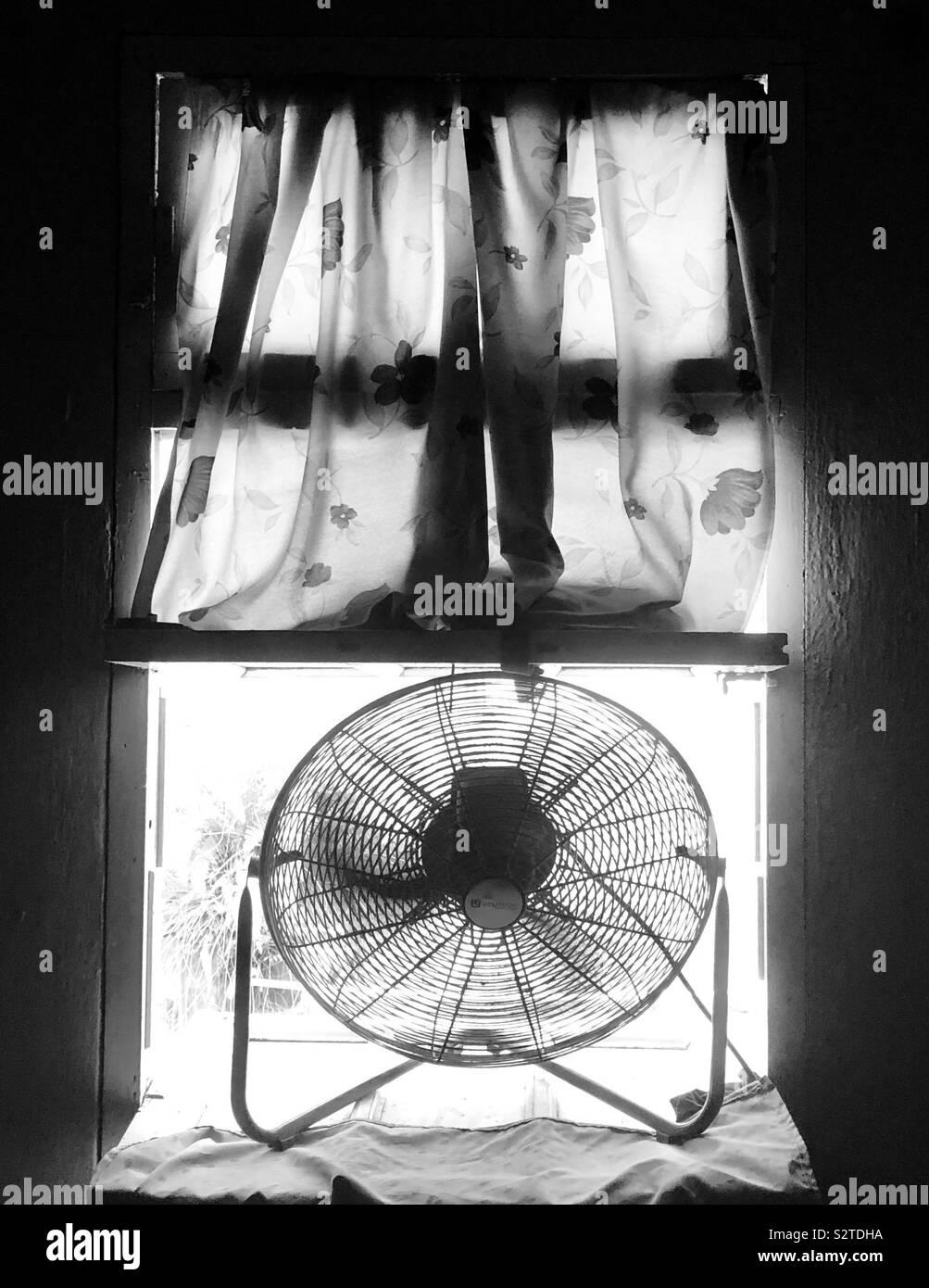 Ventilador de piso sentado en la ventana en un día caluroso y soleado. Foto de stock