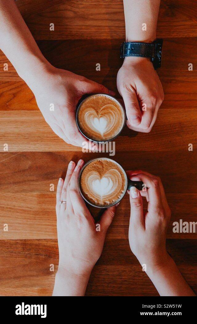 Dos tazas de café latte art en una tabla. Dos personas sosteniendo tazas de café. Foto de stock