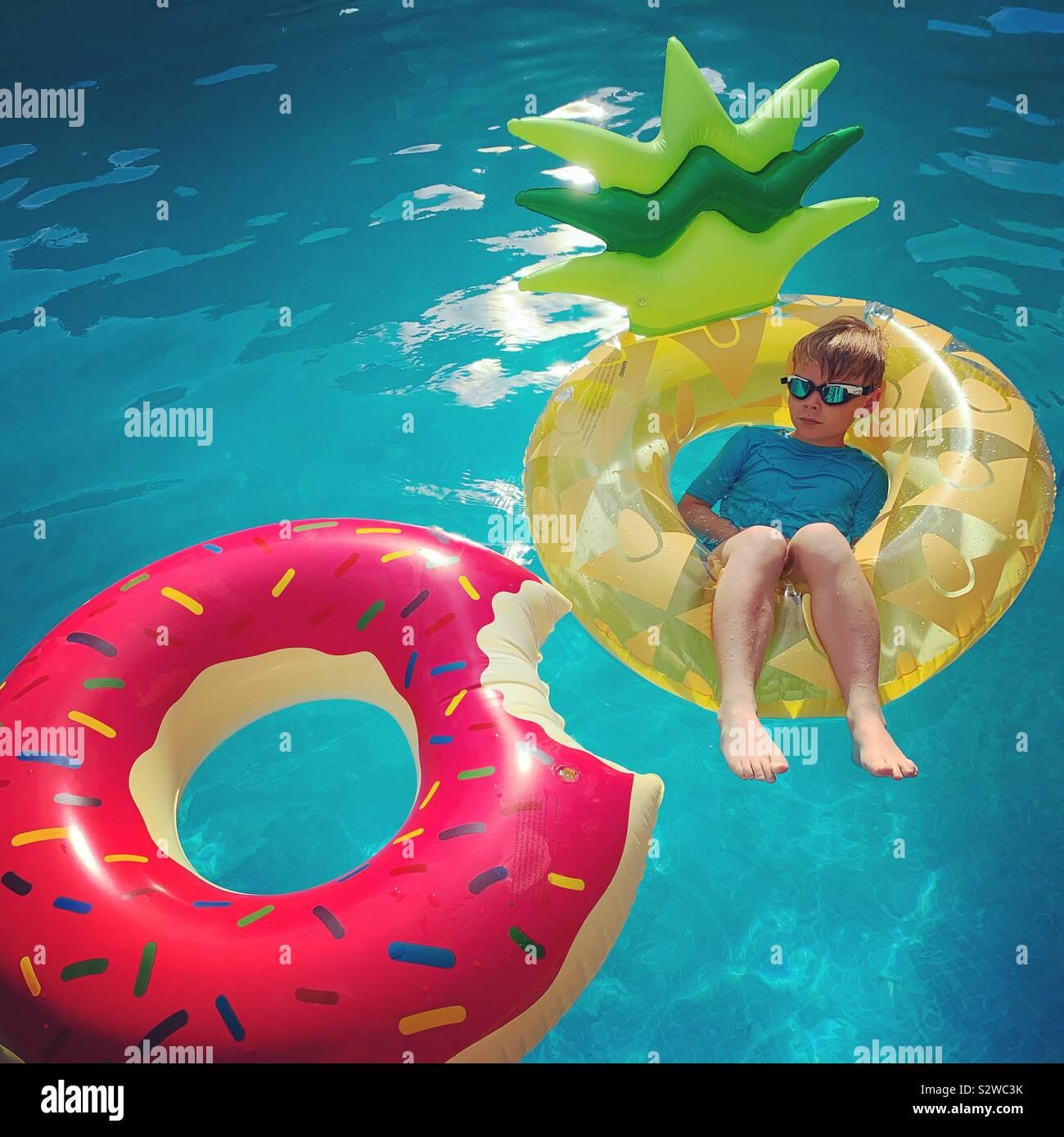 Niño sobre un flotador de piña Foto de stock