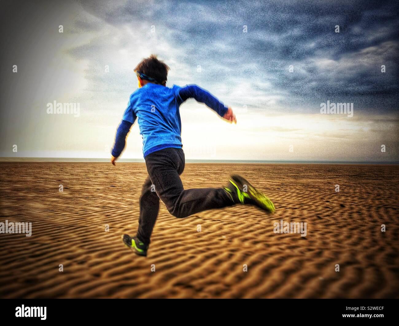 Niño corriendo en la playa, en el REINO UNIDO Foto de stock