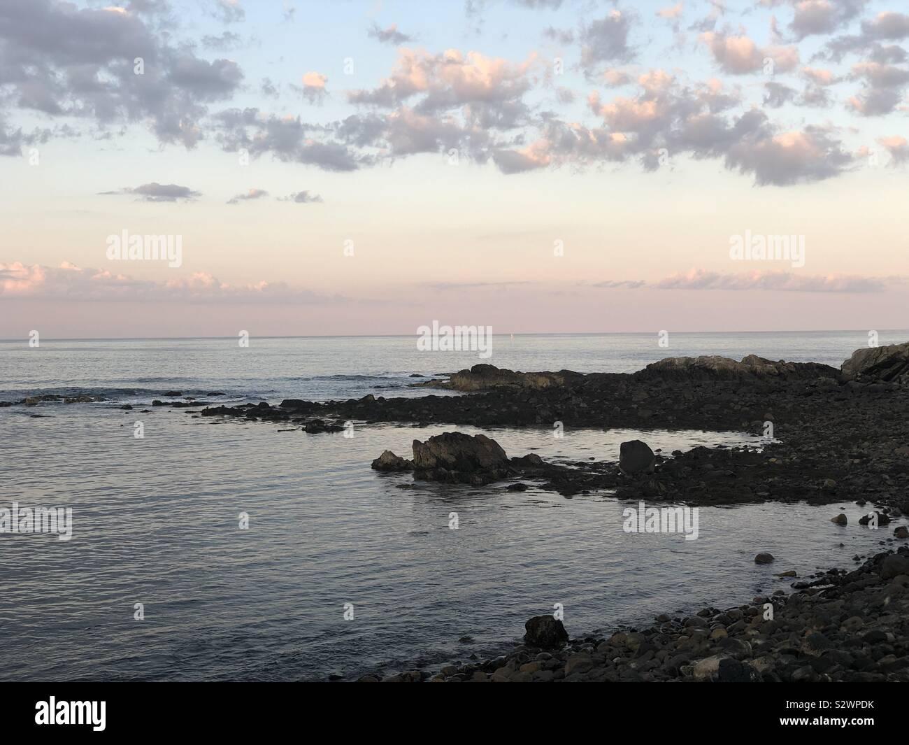 La costa de Maine, el océano, las rocas, las nubes del atardecer Foto de stock