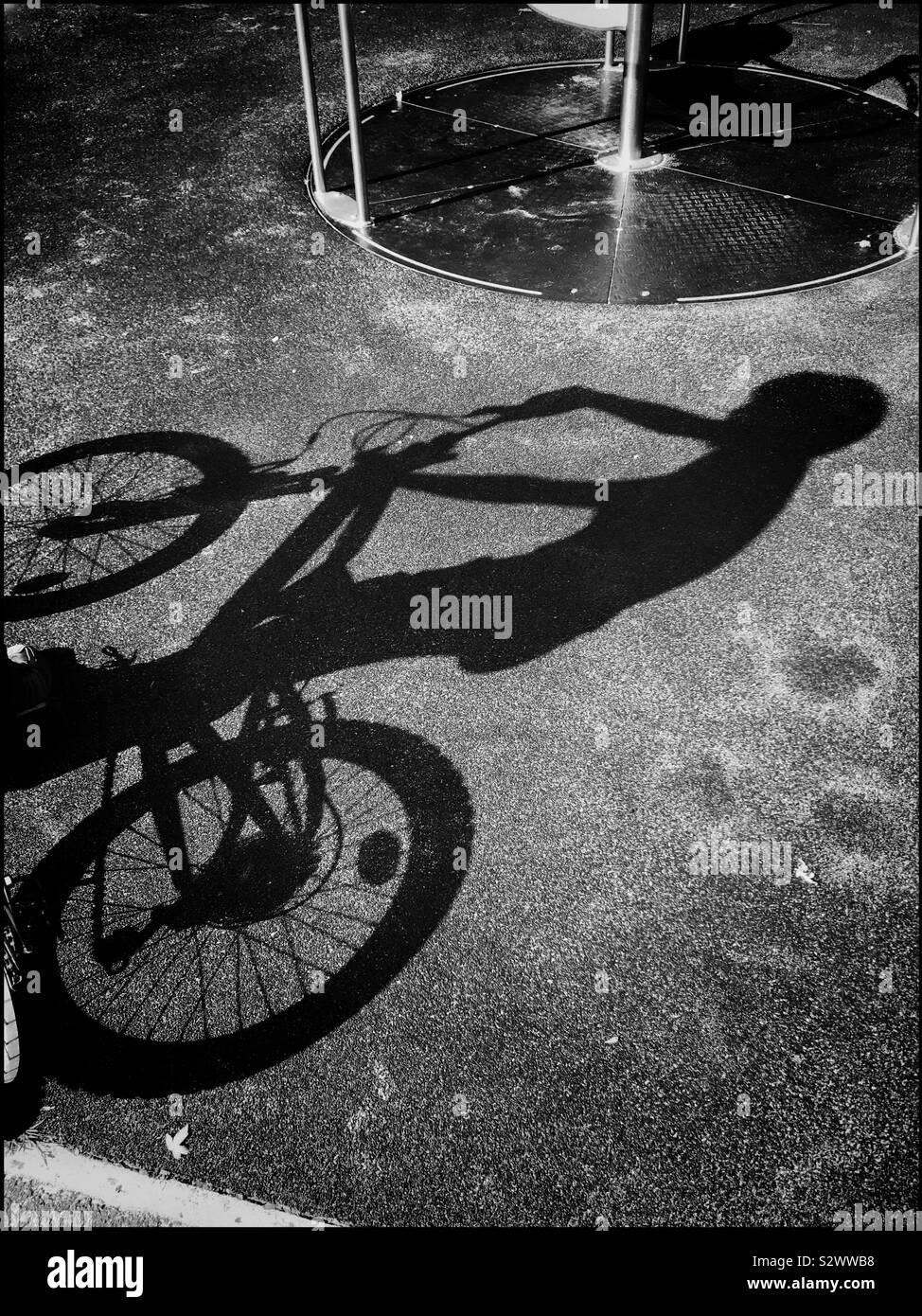 La sombra de un niño montando su bicicleta en un parque infantil. La brillante luz del sol ha creado una interesante sombra en el suelo. Foto © COLIN HOSKINS. Foto de stock