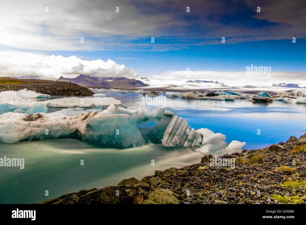 La larga exposición de una laguna en Islandia con témpanos flotantes Foto de stock
