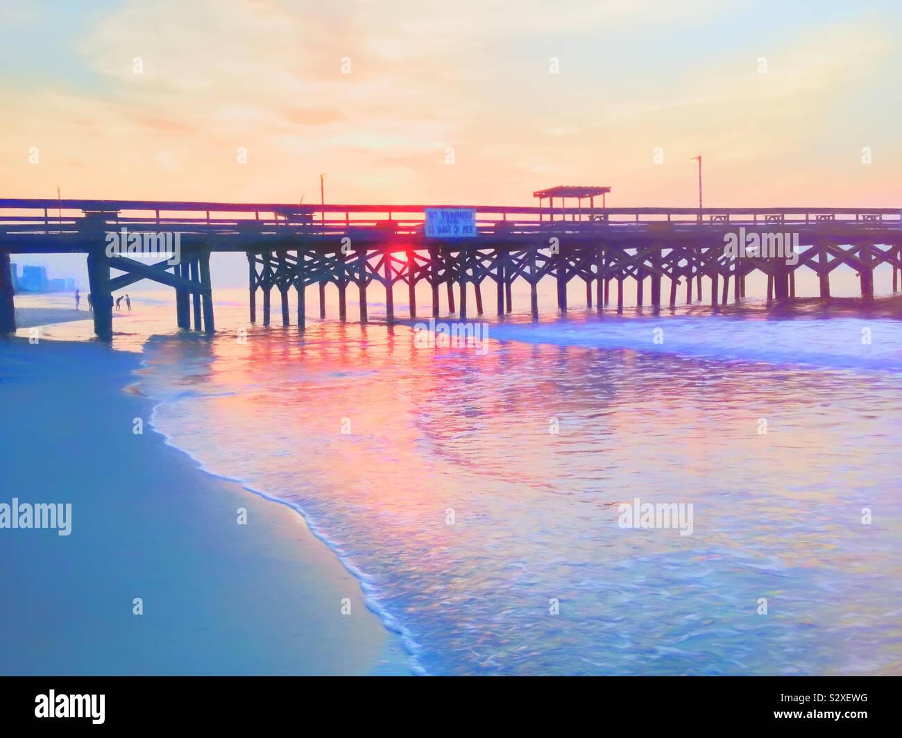 Sol detrás de un muelle en Myrtle Beach, Carolina del Sur. La gente en la playa. Foto de stock