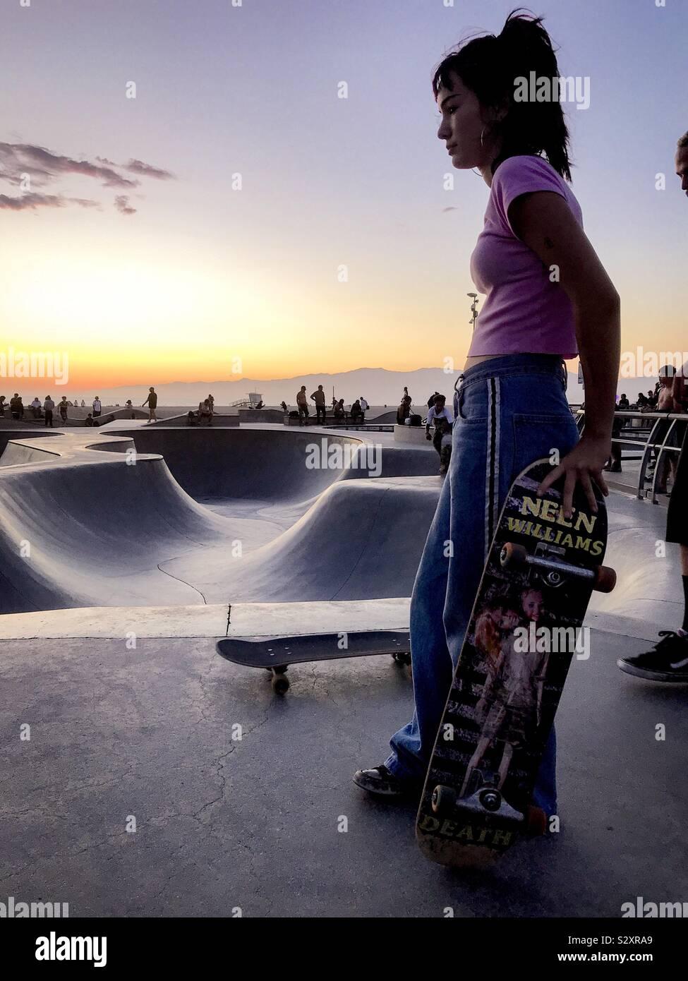 Skate girl contemplando las curvas durante la hora dorada en Venecia CA. Foto de stock