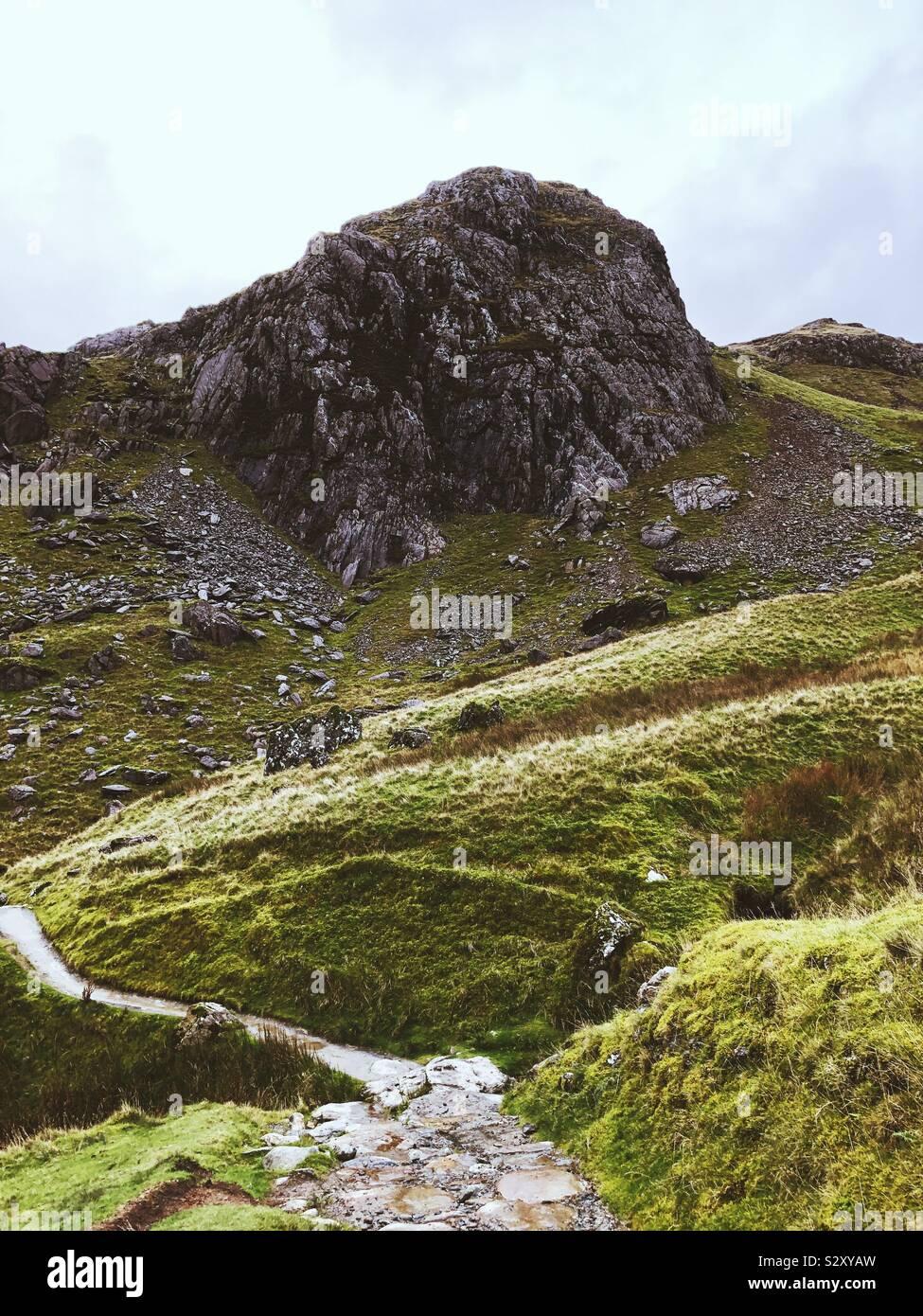 Camino al Monte Snowdon debajo de un gran acantilado Foto de stock