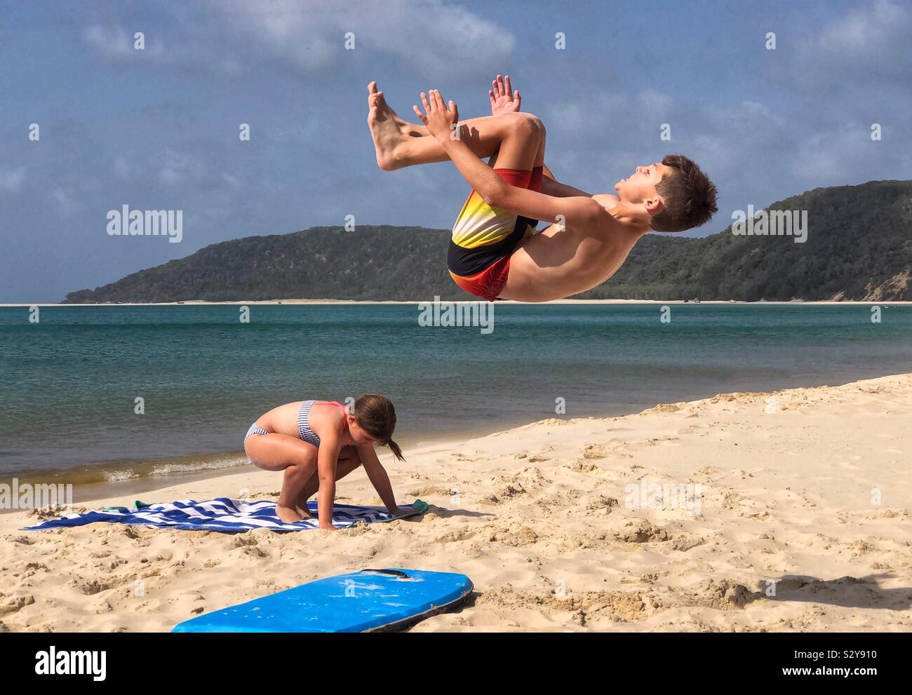 Niños jugando en la playa backflip acrobacia tumbling Foto de stock