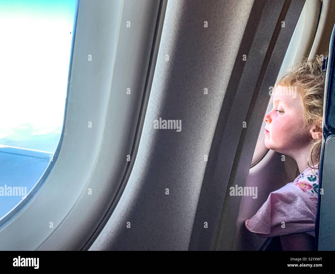 Joven en busca de un avión mientras volaba de ventana Foto de stock