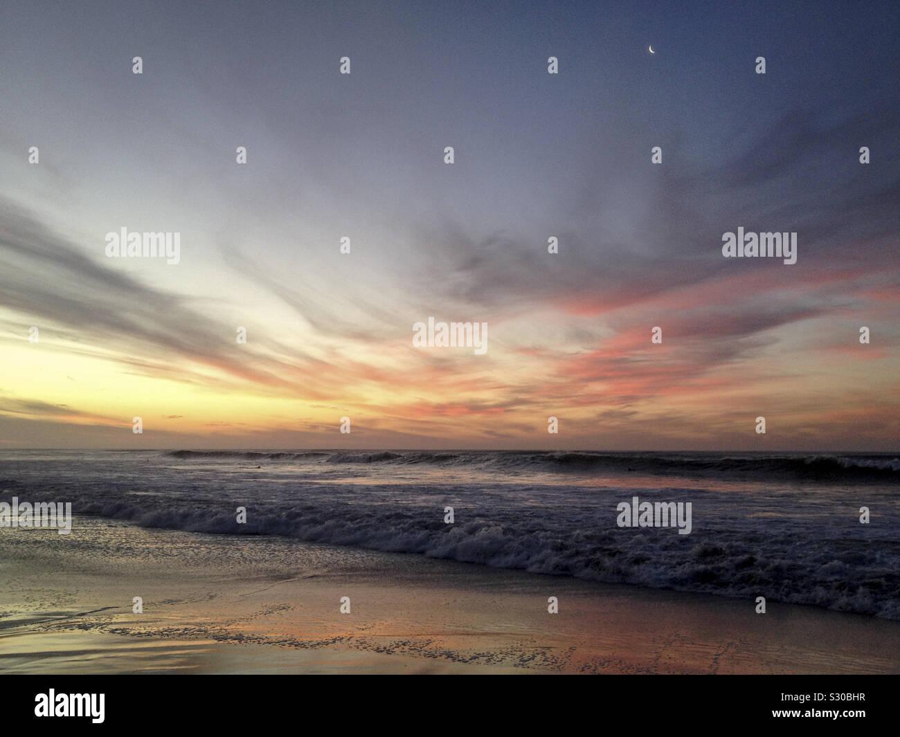 Después de la puesta del sol, con la luna en seascape Kommetjie Long Beach, Cape Town, Sudáfrica. 2019. Foto de stock