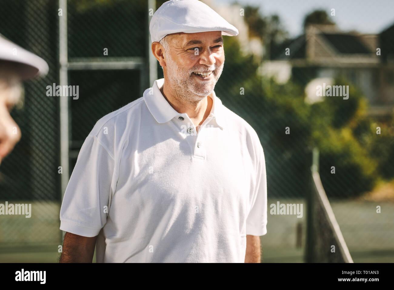 Senior alegre hombre de pie sobre una pista de tenis en un día soleado. Hombre sonriente en blanco camiseta de tenis y tapa de pie afuera. Foto de stock