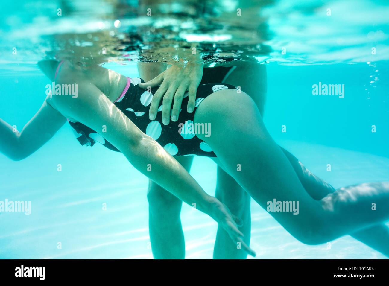 Bajo el agua foto de mujer enseñando su niña a nadar en la piscina. Chica en traje de baño aprender a nadar con un autobús en el centro de ocio. Foto de stock