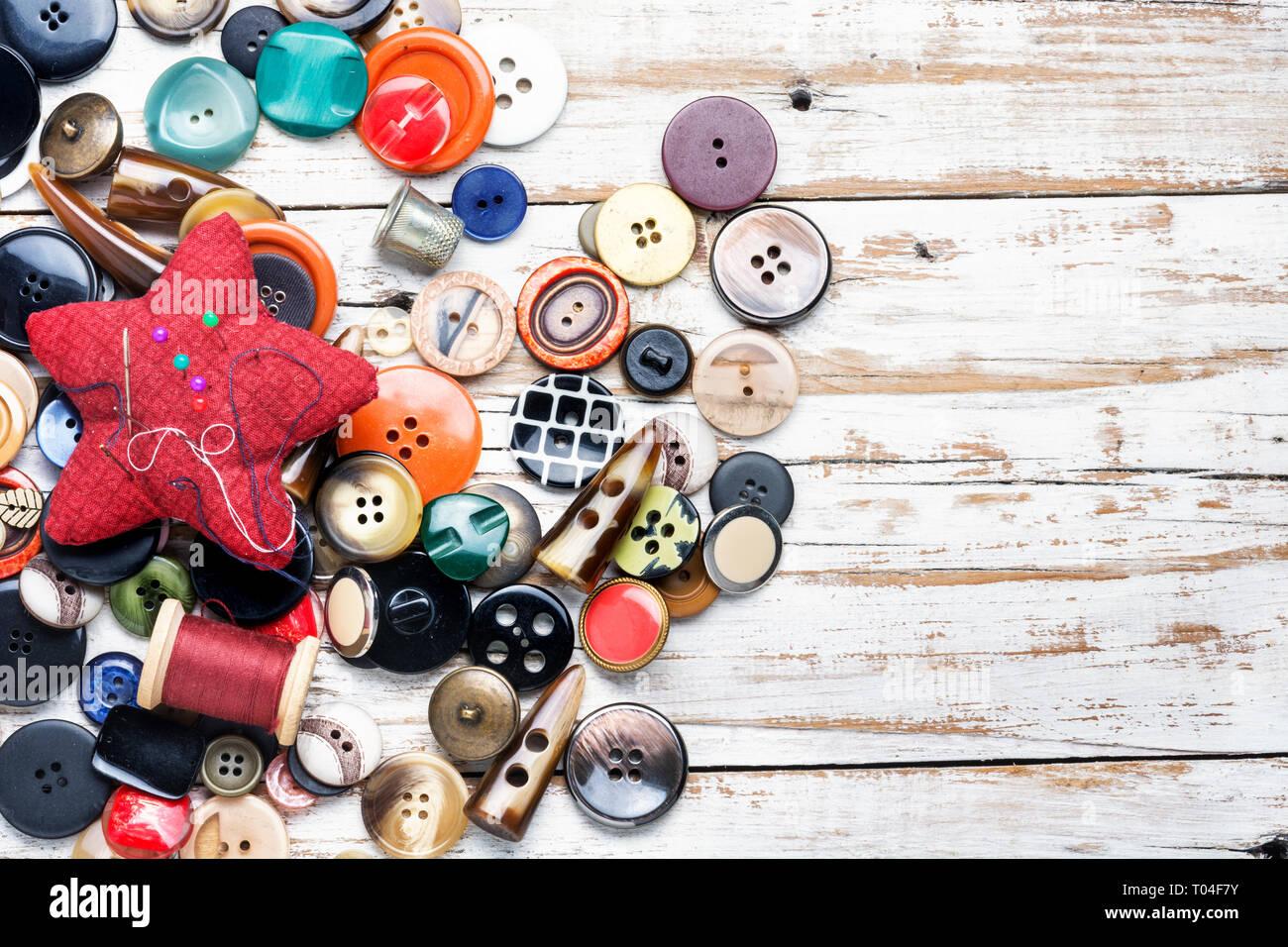Carretes de hilos y botones en la mesa de madera Foto de stock