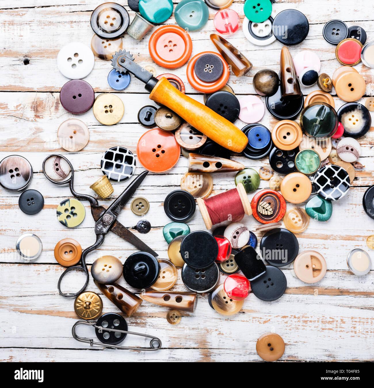 Carretes de hilos y botones en la mesa de madera.La Tijera cosiendo botones e hilo Foto de stock