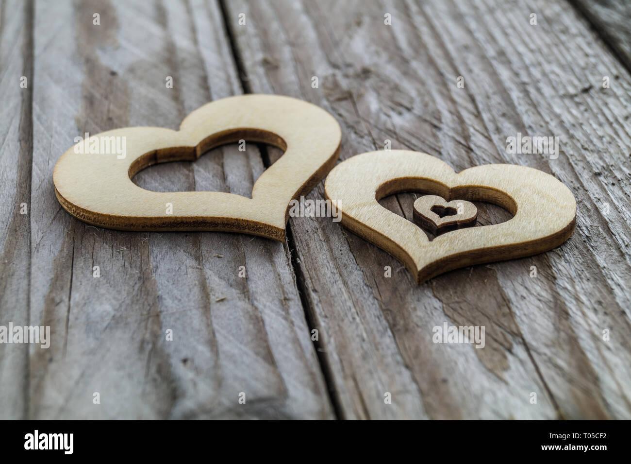Dos corazones de madera con un poco de corazón sobre una mesa de madera. Symobl para la familia y el embarazo. Foto de stock