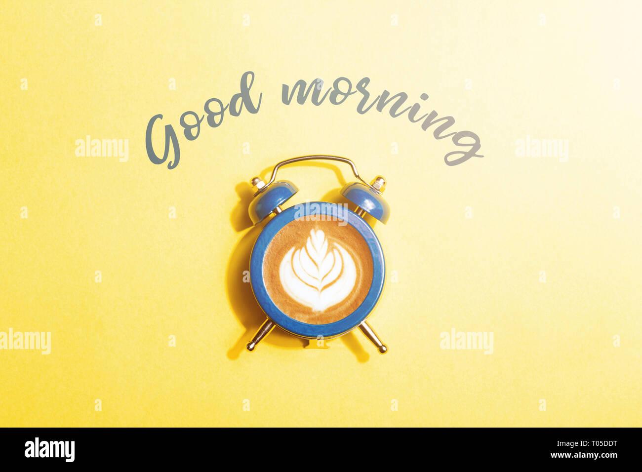 Reloj despertador con el dial de capuchino sobre fondo amarillo. Concepto de tiempo café minimalistas con inscripción de buena mañana. Foto de stock