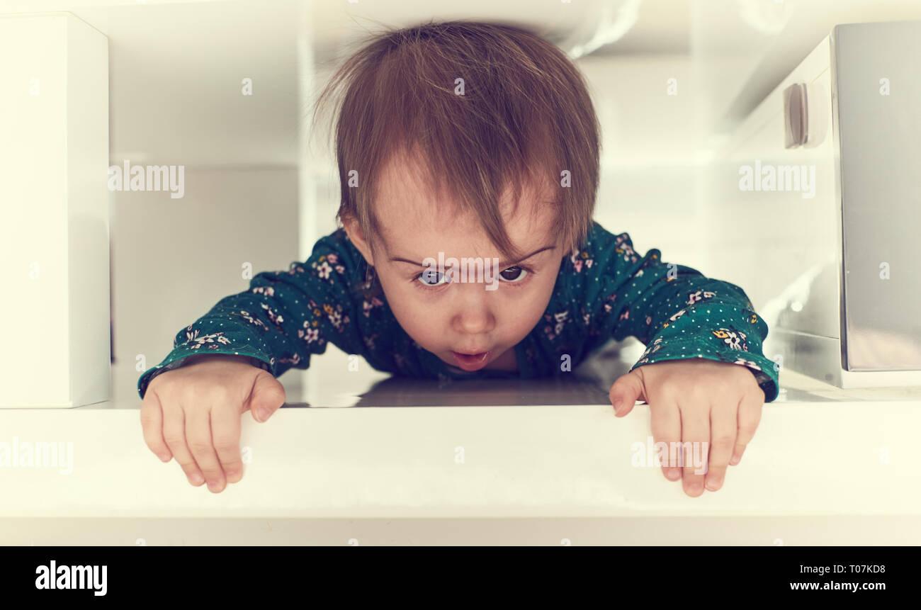 Lindo bebé niña caucásica gatear por espacio limitado bajo mesa de café hacia la cámara.Garbing borde de tabla y puling su auto. Copie el espacio en la parte derecha Foto de stock