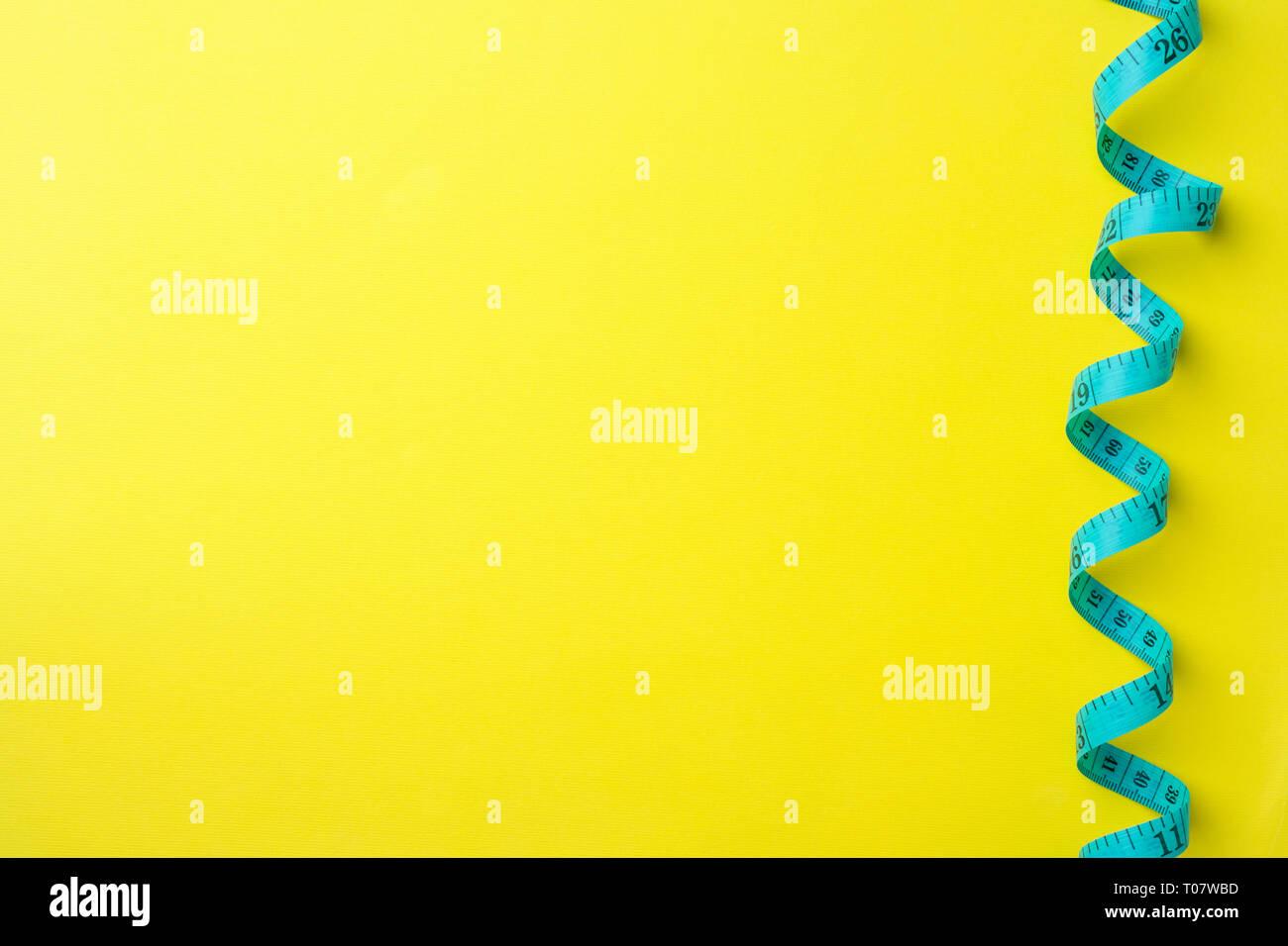 Regla centímetro plegada con compartimientos de medición sobre un fondo amarillo. Artesanía y confección concepto. Espacio de copia Foto de stock