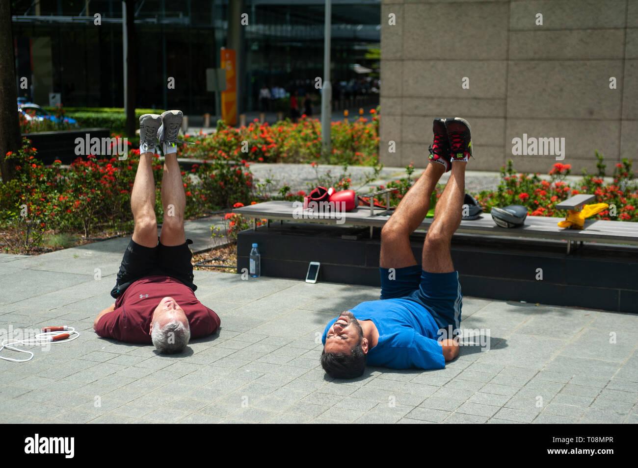 18.04.2018, Singapore, Singapur, Singapur - Dos hombres mantenerse en forma durante su descanso de almuerzo en el distrito de negocios, con circuitos de entrenamiento. 0SL180418D023C Imagen De Stock