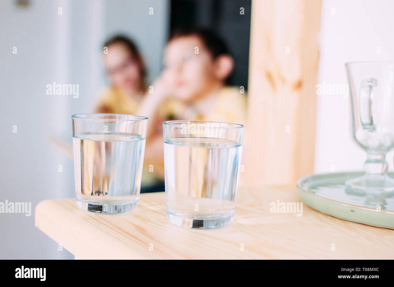 Dos vasos de agua limpia, los niños en el fondo Foto de stock