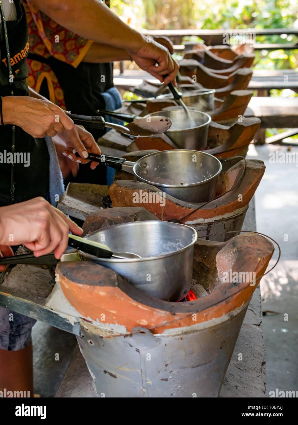 Los turistas en el Sureste asiático la lección de cocina de Laos haciendo purple arroz pegajoso en estufas de arcilla, Tamarindo escuela de cocina, en Luang Prabang, Laos Foto de stock
