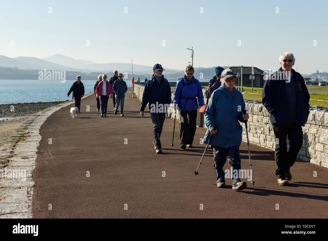 La gente caminando por el paseo marítimo en el centro de la ciudad de Beaumaris, Anglesey, Norte de Gales, Reino Unido Foto de stock