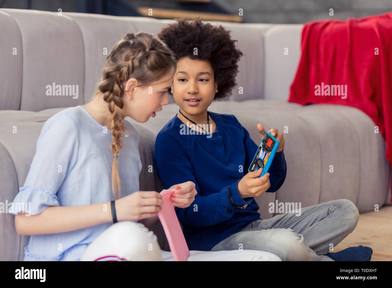 Niños alegres jugando juntos con sus gadgets Foto de stock