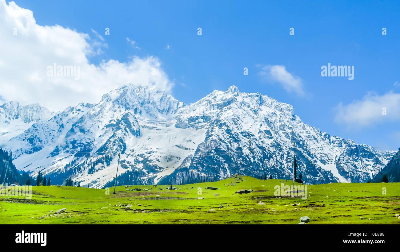 Amplia vista panorámica de picos de montañas cubiertos de nieve y el cielo azul con nubes en el valle Baisaran Mini (Suiza), Pahalgam, Cachemira, India Foto de stock