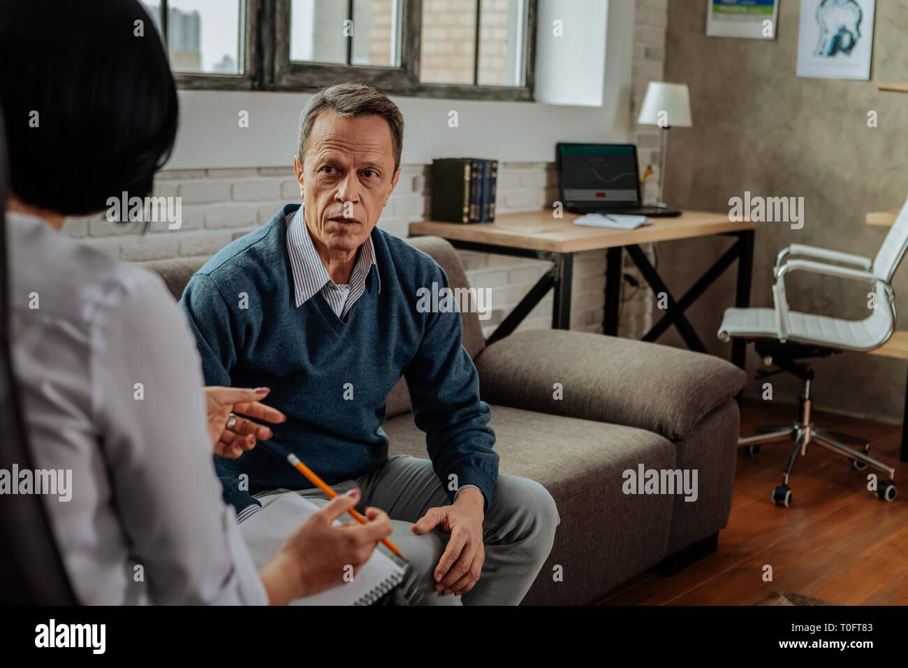 Adultos perturbados guy en Cardigan azul está conmocionada durante la conversión con el doctor Foto de stock