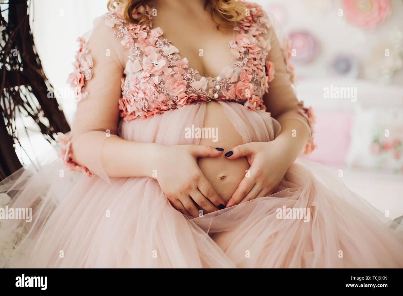 cf5b42c17 Cerca de la mujer embarazada en polvo vestido largo tocando el estómago.  Imagen De Stock