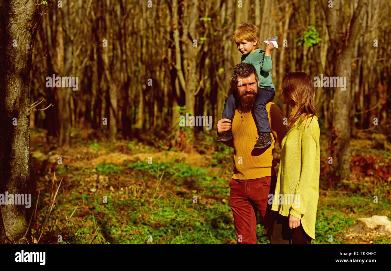 Cada día un nuevo descubrimiento. La madre y el padre sumarse pequeño hijo caminatas en el bosque, el concepto de descubrimiento. Familia de vacaciones junto a la naturaleza Imagen De Stock