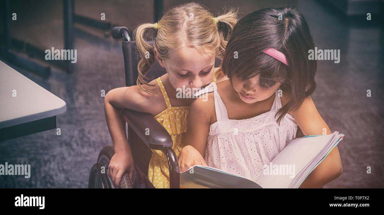 Las niñas la lectura en el aula Foto de stock