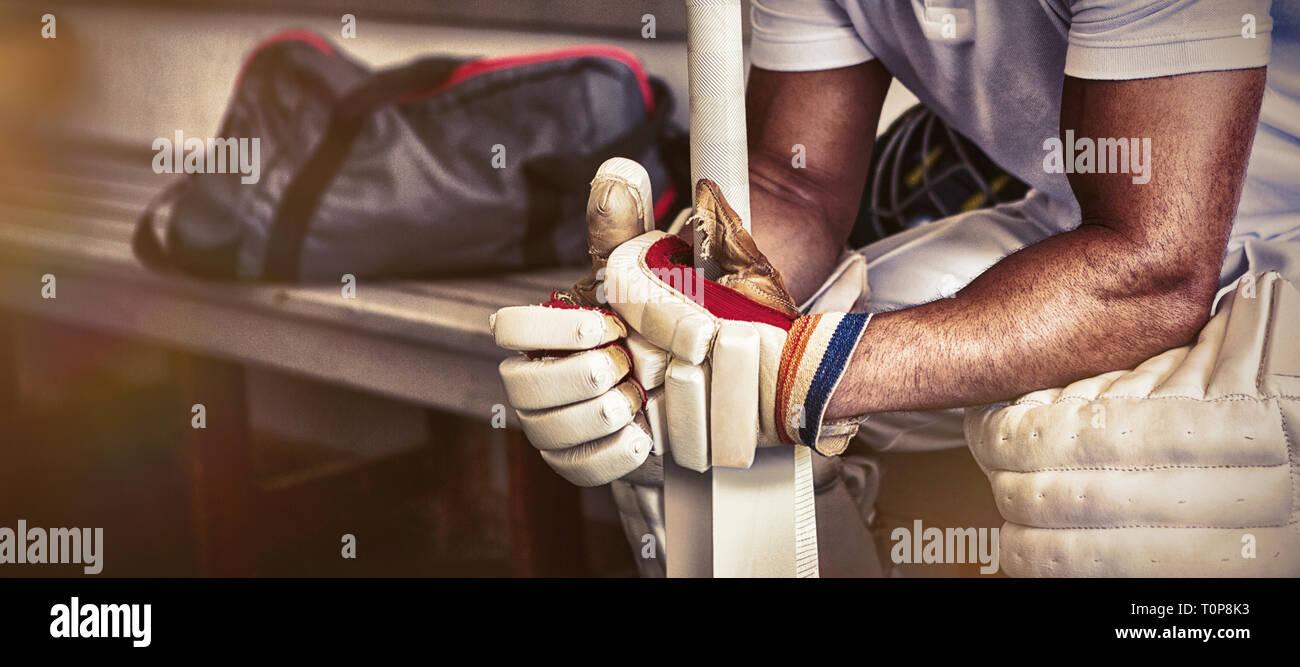Subrayó cricket jugador sentado en un banco Foto de stock