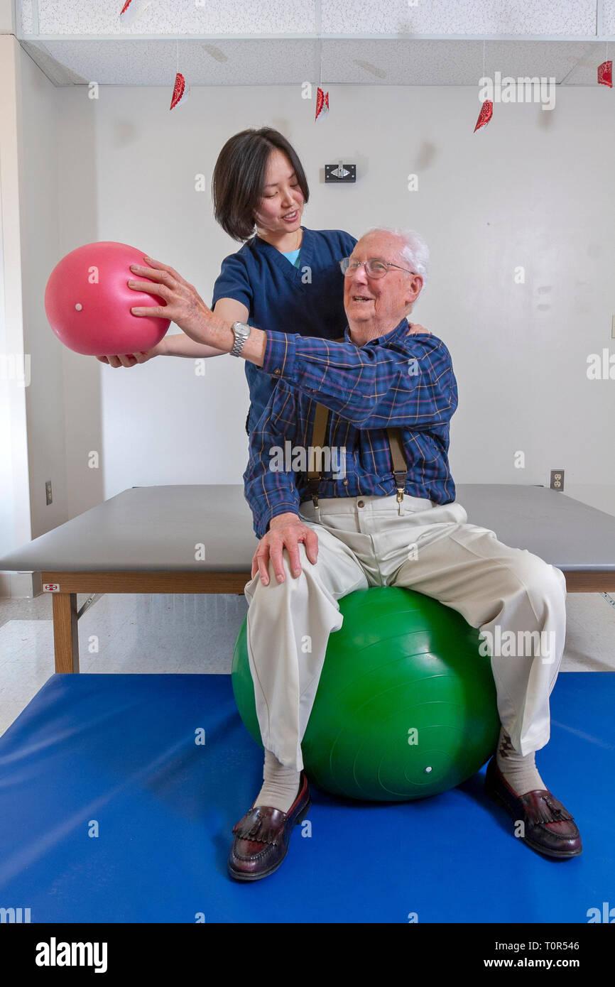 Un hombre senior en el Departamento Rehabitation del paciente en un hospital recibiendo terapia ocupacional de un terapeuta terapia de ejercicios con pelotas. Imagen De Stock