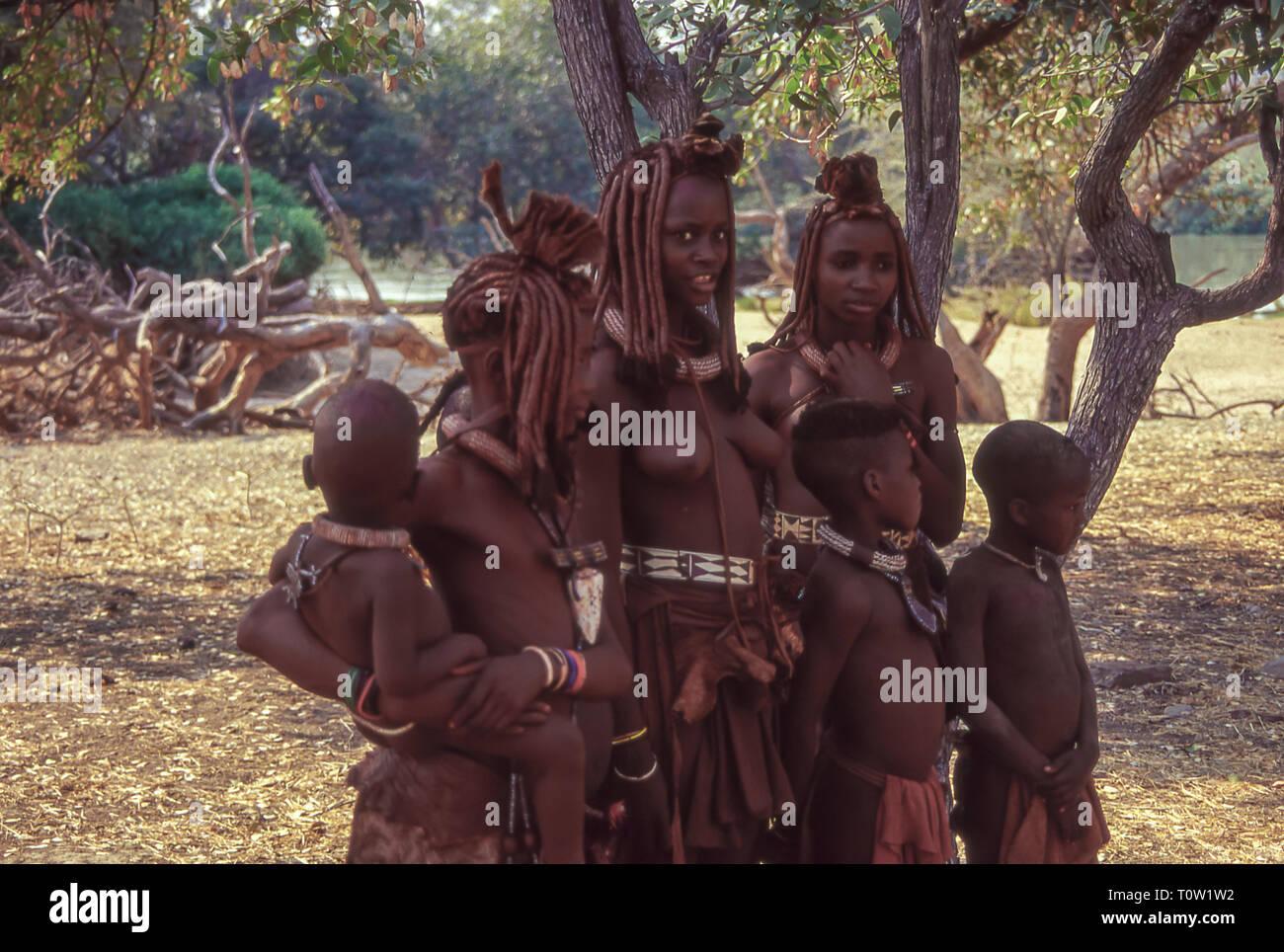 Grupo de jóvenes, mujeres y niños de la etnia Himba cerca del Epupa Falls en el río Kunene en Namibia, la frontera con Angola. Foto de stock