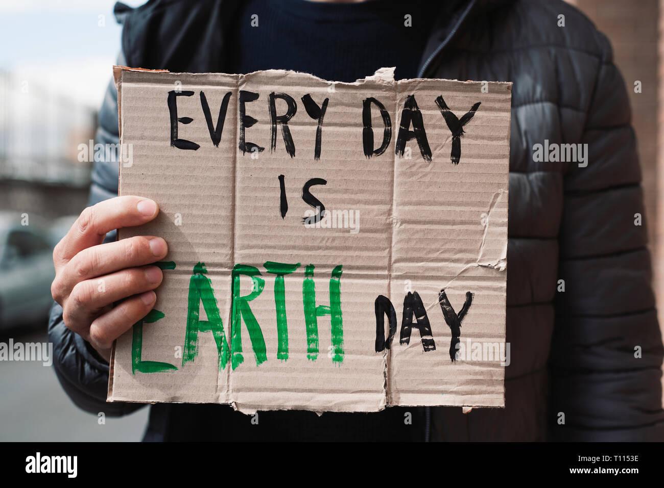 Primer plano de un joven hombre caucásico, en la calle, mostrando un cartel de cartón marrón con el texto cada día es el día de la tierra en ella manuscritas Imagen De Stock