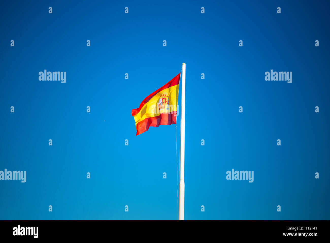 Bandera española sobre el cielo azul, sin nubes, símbolo de España Imagen De Stock