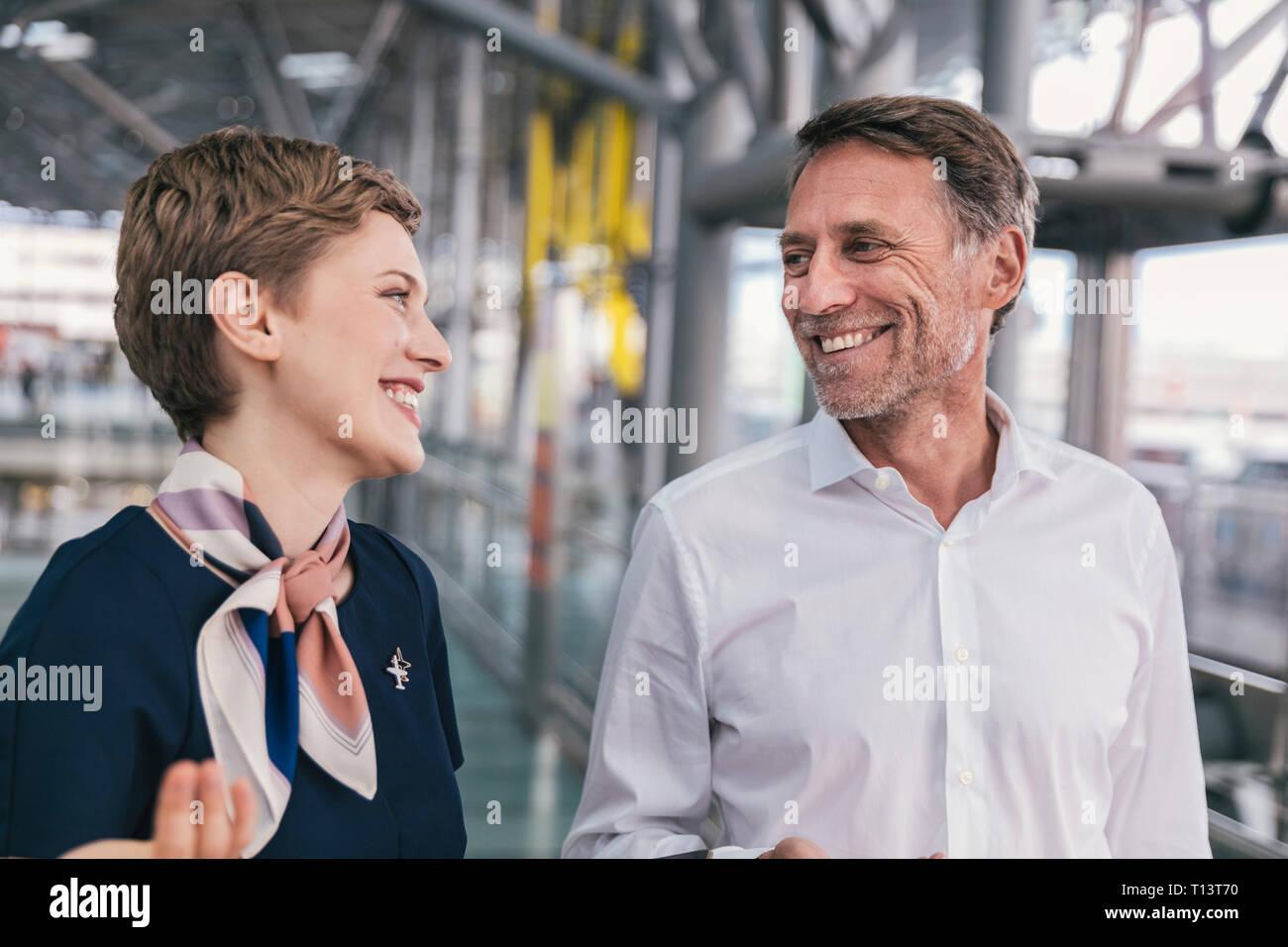 Feliz empleado de aerolínea hablando a los pasajeros en el aeropuerto. Foto de stock