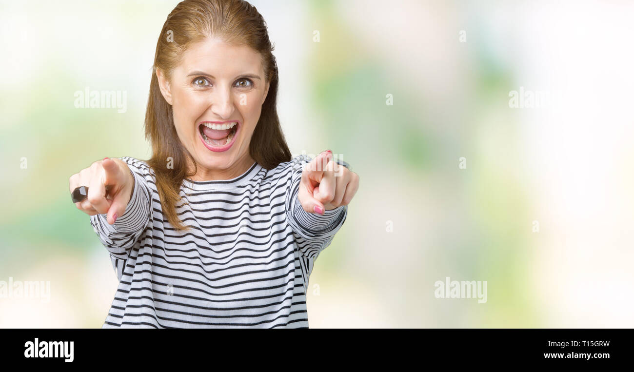 La mediana edad madura hermosa mujer vestidos de rayas suéter de invierno sobre fondo aislado apuntando hacia usted y la cámara con los dedos, sonriendo positiv Imagen De Stock