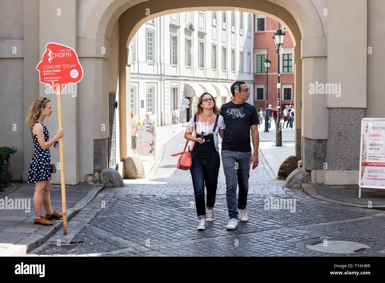 Varsovia, Polonia - Agosto 23, 2018: Street, cerca de la plaza de la ciudad vieja con la ciudad histórica arquitectura y forma de arco con la pareja caminar, mujer sosteniendo Chopin c Imagen De Stock