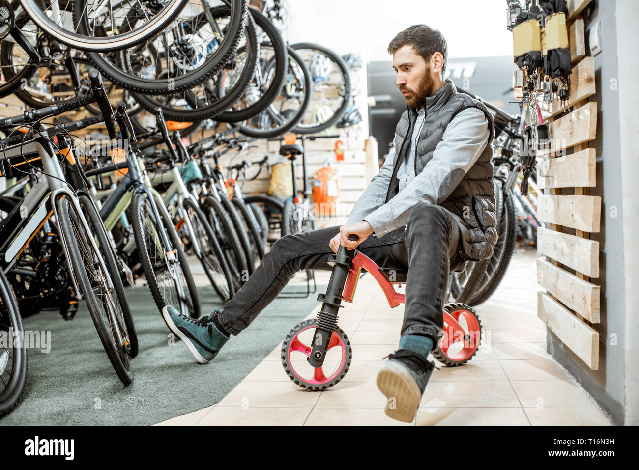 Gracioso retrato de un hombre montando bicicleta infantil en la tienda de bicicletas y equipamiento deportivo Foto de stock