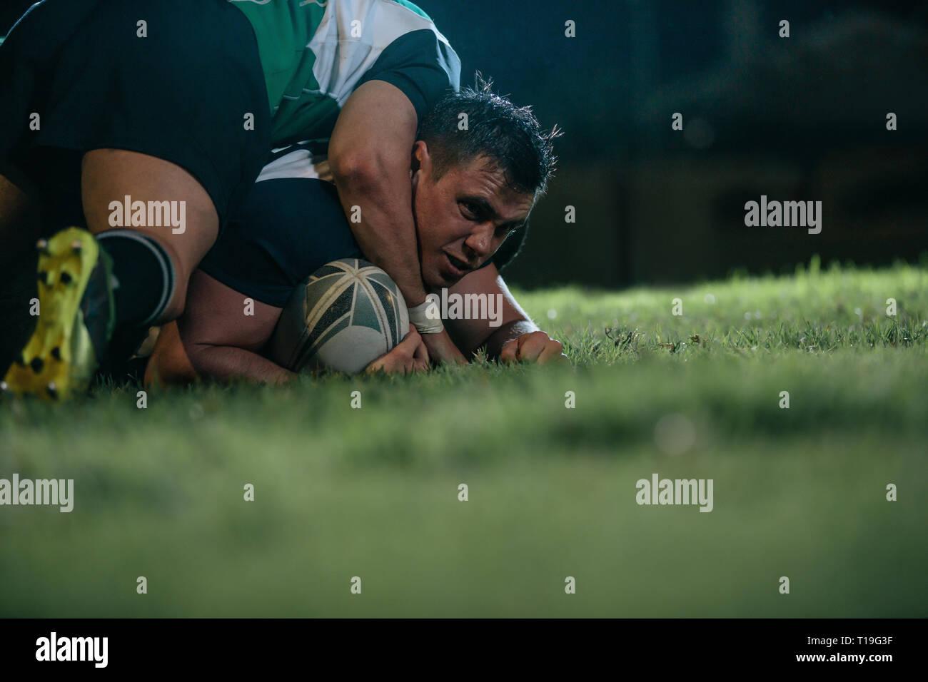 Jugador de rugby está bloqueado por los jugadores del equipo contrario. Deportes hombres pasadores abajo oponente durante el partido de rugby en la noche. Foto de stock