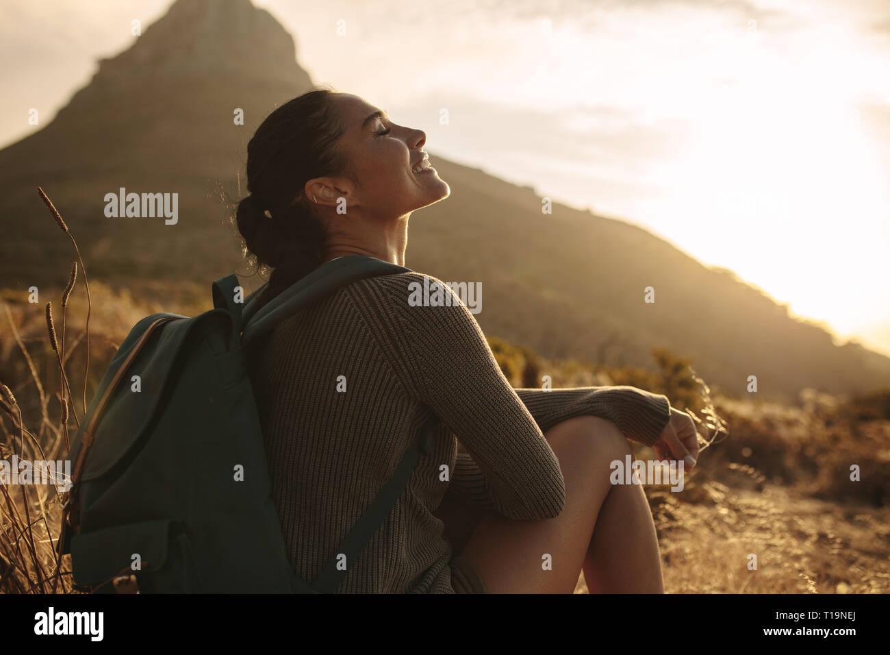 Mujer sentada en el suelo sonriendo con los ojos cerrados. Caucasian mujeres turistas tomando un descanso después de hacer senderismo en el país trail. Foto de stock